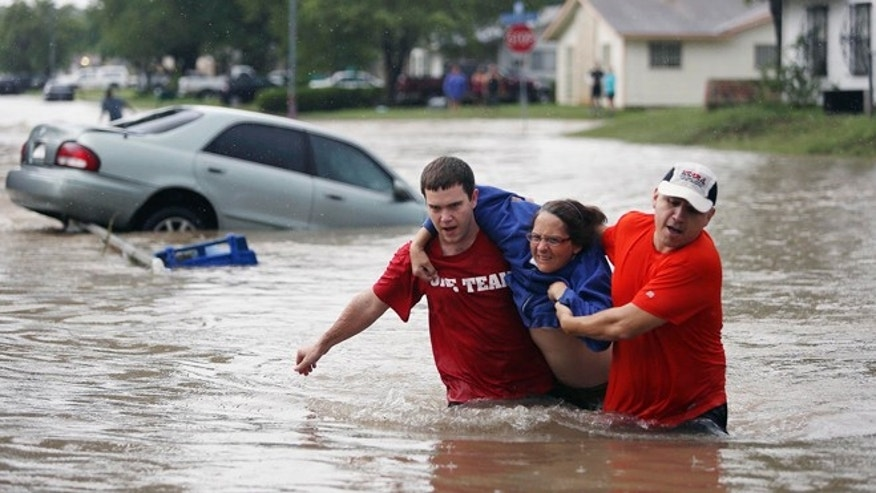 Marco Fairchild and Gary Garza help Sueann Schaller from her car Saturday, May 25, 2013 in San Antonio after she drove it into floodwaters in the Westwood Village neighborhood.