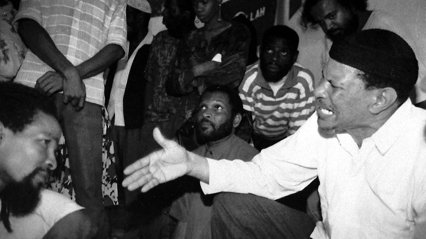 FILE - In this July 1, 1992 file photo, Yasin Abu Bakr, right, speaks with other freed members of the Jamaat al Muslimeen group that attempted a coup in Trinidad & Tobago in 1990, after their release in Port-of-Spain, Trinidad.  After years of lingering questions about the attempted coup by Bakr and 113 armed rebels, a commission appointed by the government in 2010 has been taking a fresh look into the only Islamic revolt in the Western Hemisphere.  (AP Photo/Willie Alleyne, File)