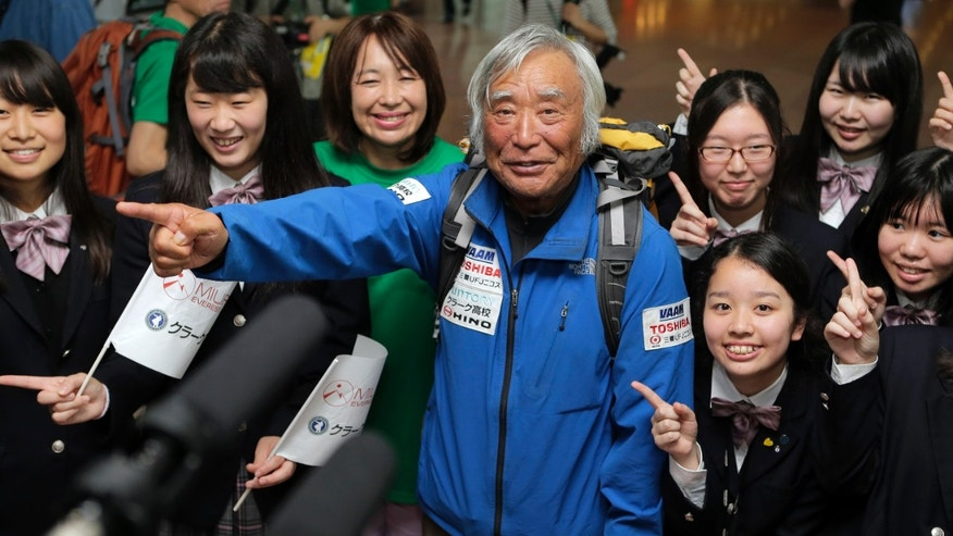 80-year-old Japanese climber Yuichiro Miura, fourth left, who became the oldest conqueror of Mount Everest on last Thursday, poses for photographers with his daughter Emiri, third left, and his CLARK Memorial International High School students upon his arrival at Haneda International Airport in Tokyo, Wednesday, May 29, 2013. Miura, a Japanese former extreme skier, conquered the mountain on May 23 despite undergoing heart surgery in January for an irregular heartbeat, or arrhythmia, his fourth heart operation since 2007. He also broke his pelvis and left thigh bone in a 2009 skiing accident. (AP Photo/Itsuo Inouye)