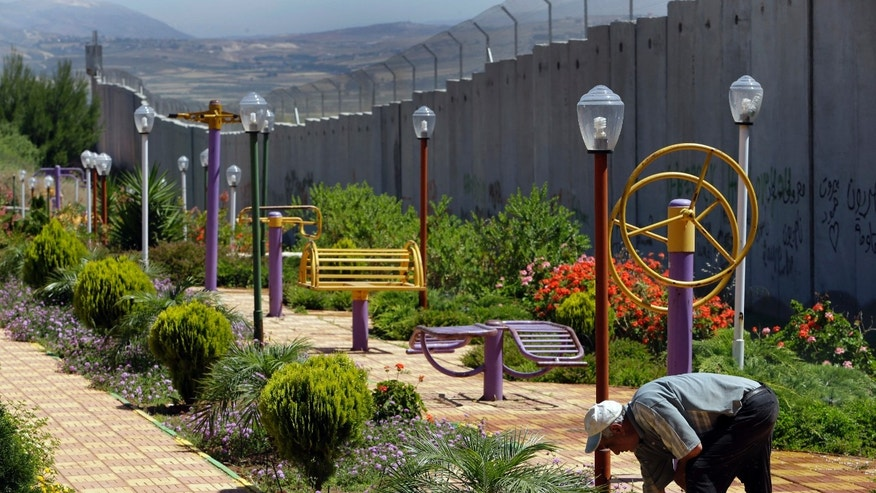In this picture taken on Thursday May 23, 2013, a Lebanese man picks flowers on Iranian-funded playground in front of a wall that was built by Israel at the Fatima Gate, where Hezbollah supporters from all over Lebanon and beyond held some of their demonstrations against Israel, in the southern village of Kafr Kila, Lebanon. A year ago, Israel built the wall along the town's stretch of the border, blocking the view of its territory and ruining the main show in town and destroying the business of the Fatima Gate Restaurant and Gift Shops. The border area was part of the 440-square-mile enclave in south Lebanon Israel had occupied for 18 years before its withdrawal in 2000. In the past decade, Iran has poured money into the area that has been cut off for the rest of Lebanon during Israel's occupation, rebuilding and expanding towns and villages. (AP Photo/Hussein Malla)