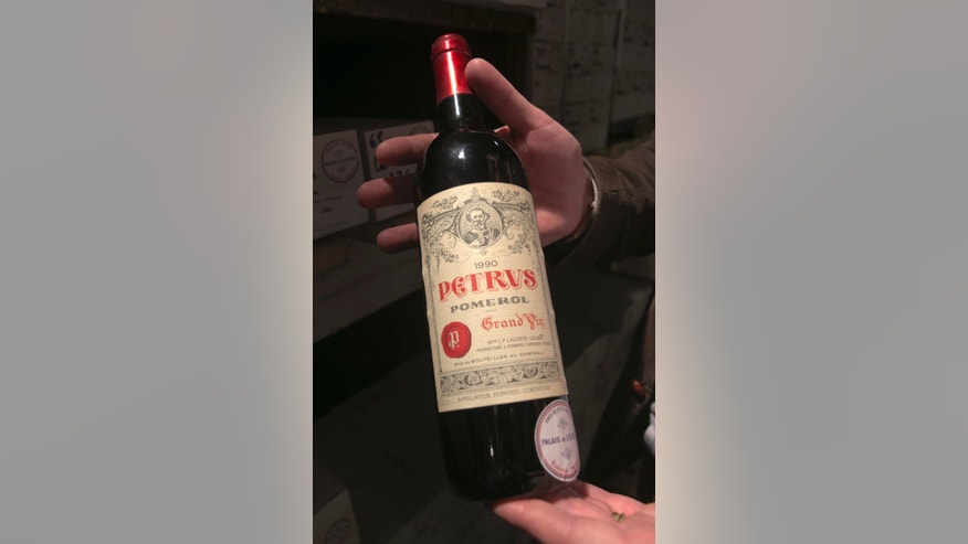 In this photo dated Tuesday May 28, 2013,  a bottle of Chateau Petrus 1990 put on auction by the French presidential Palace is displayed during an auction preview in Issy les Moulineaux, south of Paris, France. French President Francois Hollande's palace has decided to dive into its wine cellar and sell some of its treasures, to raise money and replenish its collection with more modest vintages. About 1,200 bottles,  a tenth of the Elysee's wine collection, are to be sold at Drouot auction house in Paris on Thursday and Friday. (AP Photo/Jacques Brinon)