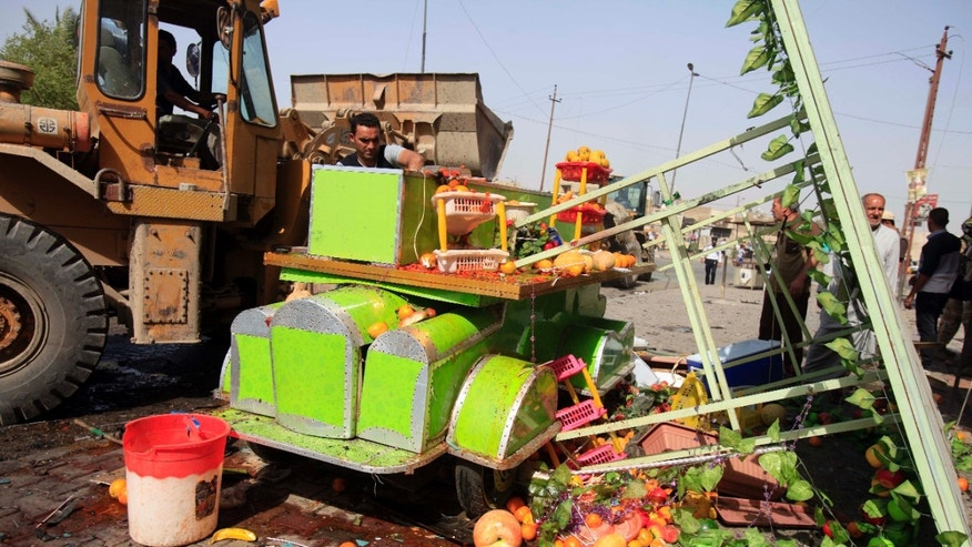 A street vendor inspects his destroyed juice cart at the scene of a bomb attack at Sadr City in Baghdad, Iraq, Tuesday, May 28, 2013. A bomb left on a Baghdad minibus and a suicide truck bomb north of the Iraqi capital killed and wounded scores of people on Tuesday, officials said. The attacks followed a particularly bloody day that left more than 70 people dead. (AP Photo/ Karim Kadim)
