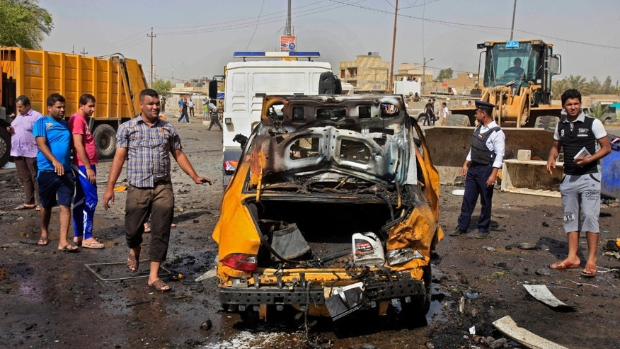 Iraqis inspect the scene of a bomb attack at Sadr City in Baghdad, Iraq, Tuesday, May 28, 2013. A bomb left on a Baghdad minibus and a suicide truck bomb north of the Iraqi capital killed and wounded dozens of people, on Tuesday, officials said. The attacks followed a particularly bloody day that left scores dead. (AP Photo/ Karim Kadim)