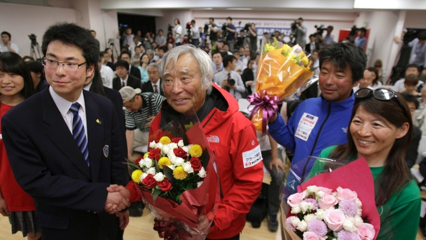 Yuichiro Miura, center, an 80-year-old Japanese mountaineer who became the oldest person to reach the top of Mount Everest last Thursday, poses for photographers before speaking at a press conference at CLARK Memorial International High School in Tokyo, Wednesday, May 29, 2013. Miura said he almost died during his descent and does not plan another climb of the world's highest peak, though he hopes to do plenty of skiing.  (AP Photo/Shizuo Kambayashi)