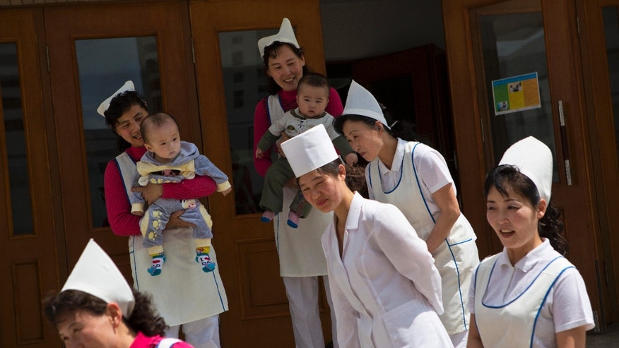 In this Monday, May 20, 2013 photo, North Korean nurses say goodbye to representatives from foreign humanitarian agencies after a U.N. and North Korean government program to give vitamin supplements and deworming pills to children at a nursery school in Pyongyang, North Korea on Child Health Day. New international sanctions aimed at thwarting North Korea's nuclear weapons program are having unintended consequences: halting money transfers by foreign humanitarian groups working to help those most in need and forcing some agencies to carry suitcases of cash in from outside. (AP Photo/David Guttenfelder)
