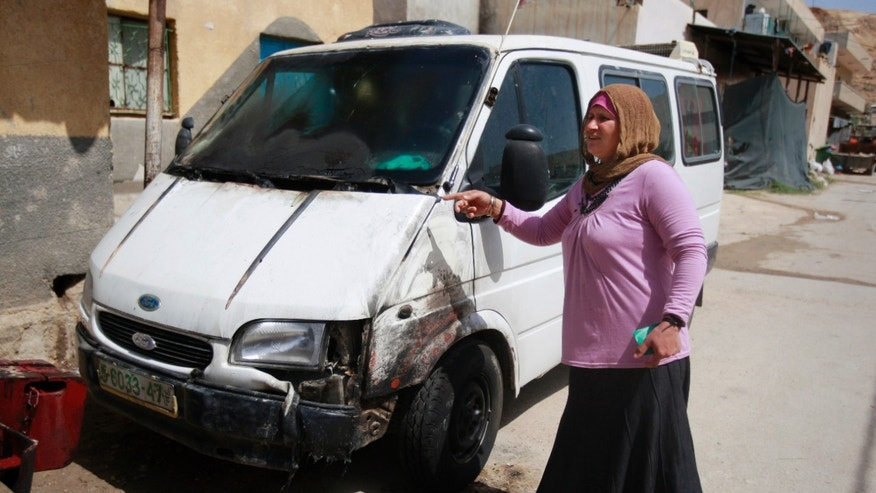 A Palestinian woman inspects a vehicle that was allegedly set ablaze by Israeli settlers in the West Bank village of Zbiedat near the town of Jericho, Wednesday, May 29, 2013. (AP Photo/Majdi Mohammed)