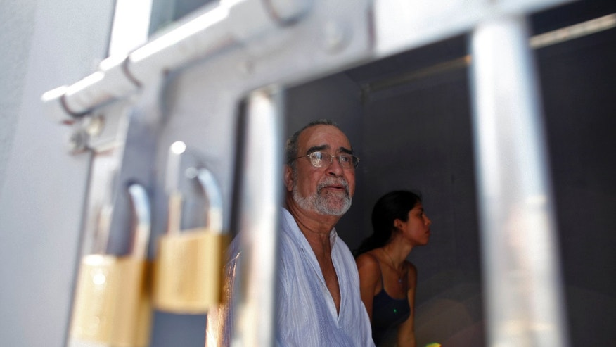 Puerto Rico salsa singer Andy Montanez and his daughter Andrea sits inside a mock cell during a protest demanding the freedom of jailed pro-independence activist Oscar Lopez Rivera in San Juan, Puerto Rico, Wednesday, May 29, 2013. Lopez was sentenced to 55 years after his conviction in 1981 on charges that included seditious conspiracy, use of force to commit robbery and interstate transportation of firearms as a member of the ultranationalist Armed Forces of National Liberation in a struggle for independence from the U.S. for the Caribbean island.  He received an additional 15 years in 1988 after he was convicted of conspiring to escape from prison in Leavenworth, Kansas.  Former President Bill Clinton offered in 1999 to release Lopez and 13 other Puerto Rican nationalists as part of what was at the time a politically sensitive clemency deal.  Under the deal, Lopez would have had to serve 10 more years in prison. He rejected the offer because it did not include two comrades who have since been released.  (AP Photo/Ricardo Arduengo)
