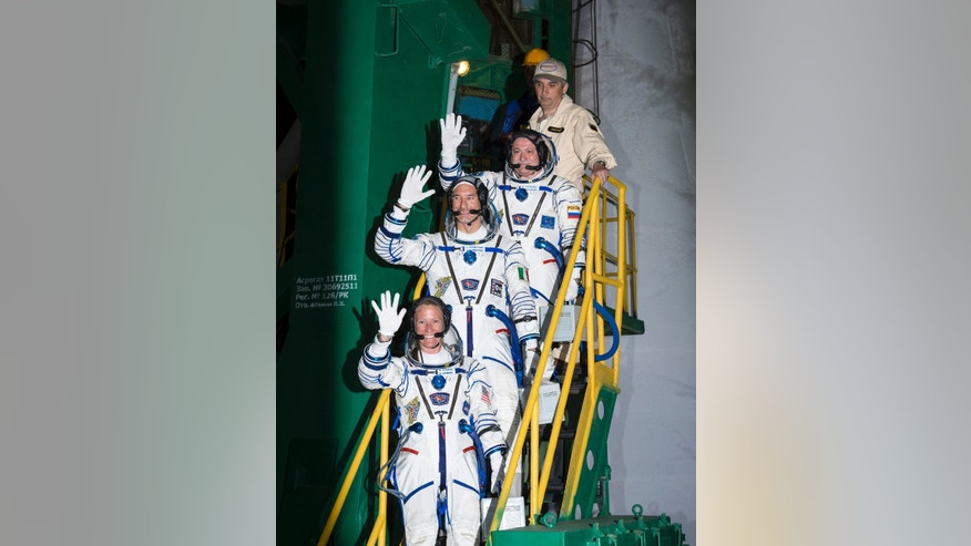 In a photo provided by NASA Expedition 36/37 Soyuz Commander Fyodor Yurchikhin of the Russian Federal Space Agency, top, Flight Engineers Luca Parmitano of the European Space Agency, center, and Karen Nyberg of NASA,  wave as they board the Soyuz rocket ahead of their launch to the International Space Station, early Wednesday, May 29, 2013,  in Baikonur, Kazakhstan.  Yurchikhin, Nyberg, and, Parmitano, will remain aboard the station until mid-November. (AP Photo/NASA, Bill Ingalls)