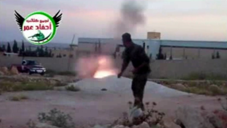 This image from amateur video obtained by a group which calls itself Ugarit News, which is consistent with AP reporting, shows a rebel fighter firing a mortar with the help of a drawstring in Aleppo, Syria, Tuesday, May 28, 2013. Europe's decision to allow member states to arm Syrian rebels and Russia's renewed pledge to send advanced missiles to the Syria regime could spur an arms race in an already brutal civil war and increasingly turn it into a East-West proxy fight. Britain promises not to transfer any arms before diplomacy is given a chance in Syria peace talks expected next month, while a top rebel commander says he needs Western anti-aircraft and anti-tank missiles now to prevent more regime gains on the battlefield. (AP Photo/Ugarit News via AP video)
