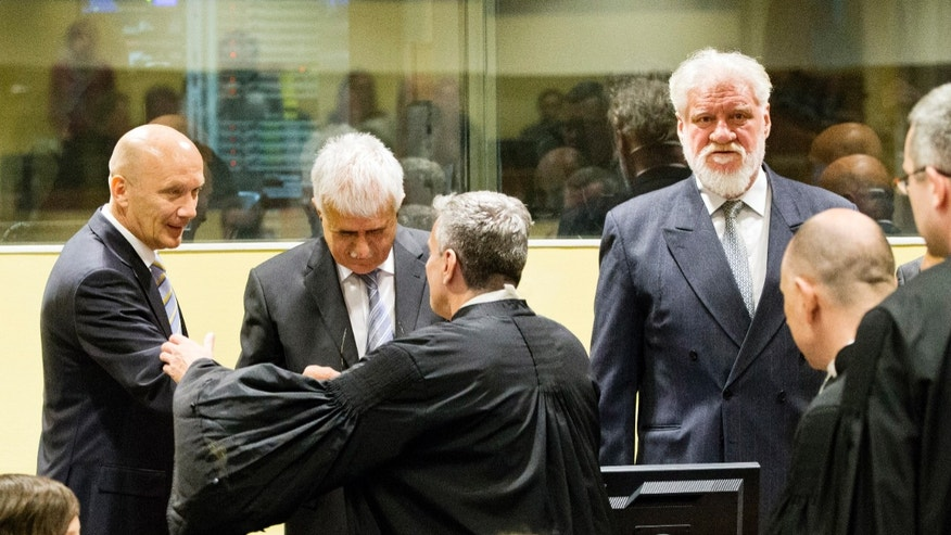 Bosnian Croat Jadranko Prlic, back row left, shakes hands with his lawyer, next to Bruno Stojic, back row center, and Slobodan Praljak, back row right, prior to their judgment at the Yugoslav war crimes tribunal (ICTY) in The Hague, Netherlands, Wednesday May 29, 2013. The ICTY is set to deliver verdicts in the long-running trial of six senior Bosnian Croats on charges of crimes against Muslims and Serbs as they tried to carve out a Croat state in Bosnia during the country's 1992-95 war. Prosecutors have asked for sentences of up to 40 years for the suspects. (AP Photo/Jiri Buller, Pool)