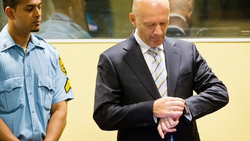 Bosnian Croat Jadranko Prlic, right, looks at his watch prior to his judgment at the Yugoslav war crimes tribunal (ICTY) in The Hague, Netherlands, Wednesday May 29, 2013. The ICTY delivers verdicts in the long-running trial of six senior Bosnian Croats on charges of crimes against Muslims and Serbs as they tried to carve out a Croat state in Bosnia during the country's 1992-95 war. Prosecutors have asked for sentences of up to 40 years for the suspects. (AP Photo/Jiri Buller, Pool)