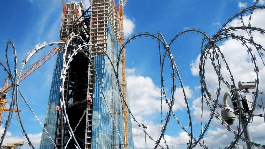 In this Aug. 27, 2012 file photo the new headquarter of the European Central Bank rises behind barbed wire in Frankfurt, German. The European Central Bank says the continent's financial system remains fragile and exposed to risks, including a downturn in markets as well as trouble among banks as they face more bad loans in a weak economy.