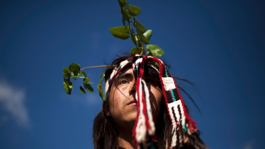 "In this Feb. 17, 2013 photo, Gerardo Purran Heiquillan, 20, poses for a portrait as he rests from dancing at a ""Guillatun,"" a spiritual ceremony to ask for the well-being of the clan and strengthen ties in the Collico community in Ercilla, Chile. In the past five years, reported acts of violence from the Mapuche land struggle have escalated 10 times over, prompting a police response that the indigenous group say has been heavy handed and abusive. (AP Photo/Rodrigo Abd)"