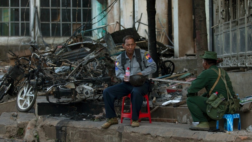 A policeman and an army officer guard a burned mosque in Lashio, northern Shan State, Myanmar, Wednesday, May 29, 2013.Hundreds of Buddhist men on motorcycles waved iron rods and bamboo poles and threw rocks in the northeastern Myanmar town on Wednesday, a day after the mosque and a Muslim orphanage were torched in a new wave of violence targeting the religious minority.  (AP Photo/Gemunu Amarasinghe)