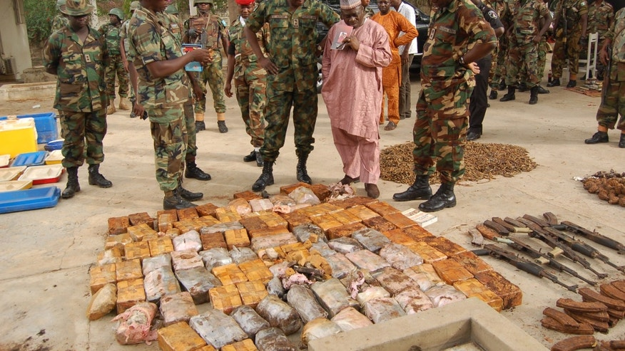This photo released by the Nigerian Army claims to show soldiers and civilians inspecting a displayed arms cache recovered from a house in Kano, Nigeria, Thursday, May 30, 2013. Nigeria's military and secret police say they've discovered an arms cache in the north's largest city they say belongs to members of the Lebanese political party and militant movement Hezbollah. Officials showed journalists the cache of weapons Thursday. The arms, later shown on the state-run Nigerian Television Authority, appeared to include badly corroded rocket-propelled grenades, land mines, hand grenades and assault rifle magazines. (AP Photo/Nigerian Army)