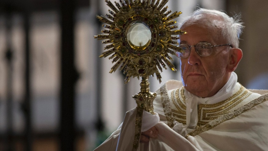 Pope Francis holds a monstrance containing a Holy Host at the end of the Corpus Domini procession from St. John at the Lateran Basilica to St. Mary Major Basilica to mark the feast of the Body and Blood of Christ, in Rome, Thursday, May 30, 2013. The event is dedicated to the mystery of the Eucharist and concludes the cycle of feasts following Easter. Pope Francis celebrated the evening Mass at St. John in Lateran Basilica then traveled a short distance in a procession to St. Mary Major Basilica. (AP Photo/Alessandra Tarantino)