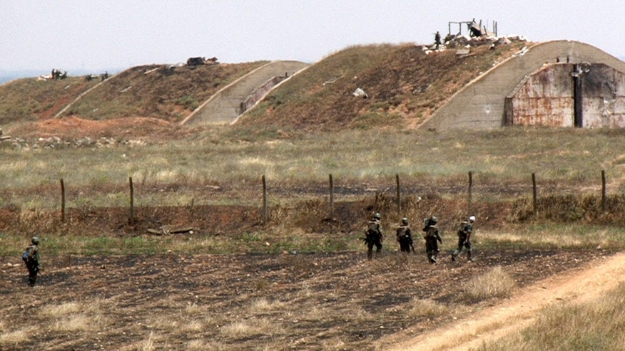 This photo released by the Syrian official news agency SANA, shows Syrian forces loyal to Syrian President Bashar Assad at the Dabaa military air base, in Homs province, Syria, Thursday, May 30, 2013. The Britain-based Syrian Observatory for Human Rights reported ongoing clashes in the town on Thursday. The Observatory called for urgent aid to the injured inside the town, most of which is now controlled by Assad's troops, including the Dabaa military air base just outside Qusair. (AP Photo/SANA)