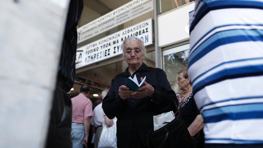 A pensioner looks at her bank book as she waits outside Greece's largest Social Security Organisation (IKA) in Athens, Friday, May 31, 2013. Hundreds of retirees waited in line for hours outside IKA offices Friday, after missing a deadline to renew their pension registration as part of an effort in the bailed out country to combat benefit fraud.  (AP Photo/Petros Giannakouris)