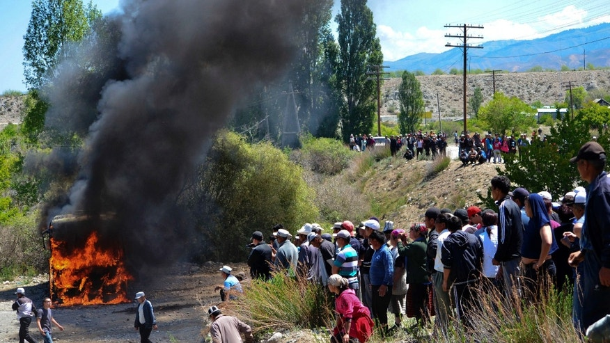 Protesters surround a burning truck in Kyrgyz town of Barskoon on Friday, May 31, 2013. Hundreds of protesters have stormed the office a gold mine run by a Canadian-based company, demanding its nationalization and more social benefits. About 2,000 people descended on the office of the Kumtor mine operated by Centerra Gold in protests that have been going on for several days. Police arrested 80 protesters Thursday night after several hundred, some on horseback, entered a power transformer unit and cut off electricity to the mine for several hours. (AP Photo/Abylay Saralayev)