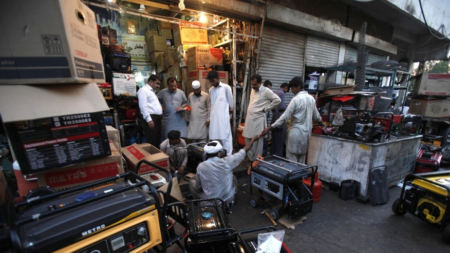 In this picture taken on Tuesday, May 28, 2013, Pakistani customers buying and getting their generators fixed in Rawalpindi, Pakistan. The government spends about $1 billion in foreign currency each month to import oil to run its power plants, another drain on foreign reserves. Burning oil is the most expensive way to generate electricity and Pakistan has reserves of natural gas. In the long run, the country will have to invest tens of billions of dollars to build huge new hydroelectric plants and convert oil burning plants to less expensive coal or gas. Pakistan faces severe electricity shortages with some parts of the country going without power for up to 20 hours a day.(AP Photo/B.K. Bangash)