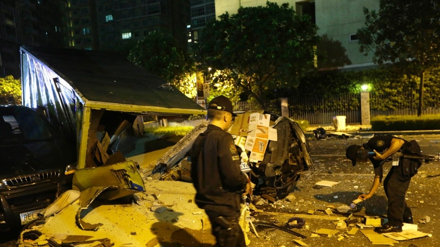 Police examine the scene after an explosion ripped through an apartment in the upscale district of Taguig city, east of Manila, Philippines, Friday, May 31, 2013. A loud explosion ripped through an apartment in Manila on Friday night, and a radio report said at least three people were killed by falling debris that hit a passing delivery van. (AP Photo/Bullit Marquez)