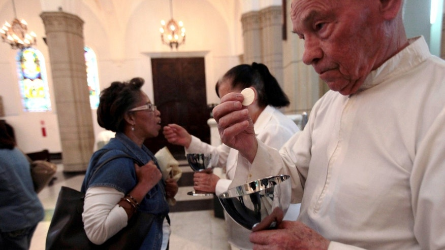 In this May 29, 2013 photo, a Eucharistic Minister holds up a host during communion as Mass is celebrated at a Catholic church in Caracas, Venezuela. Church officials say food shortages and foreign exchange restrictions are causing a lack of ingredients needed to celebrate Mass: altar wine as well as wheat to produce communion wafers. The church's concerns echo those of Venezuelans in general, who have struggled to find goods such as toilet paper and staple food items like milk, sugar and cooking oil.  (AP Photo/Fernando Llano)