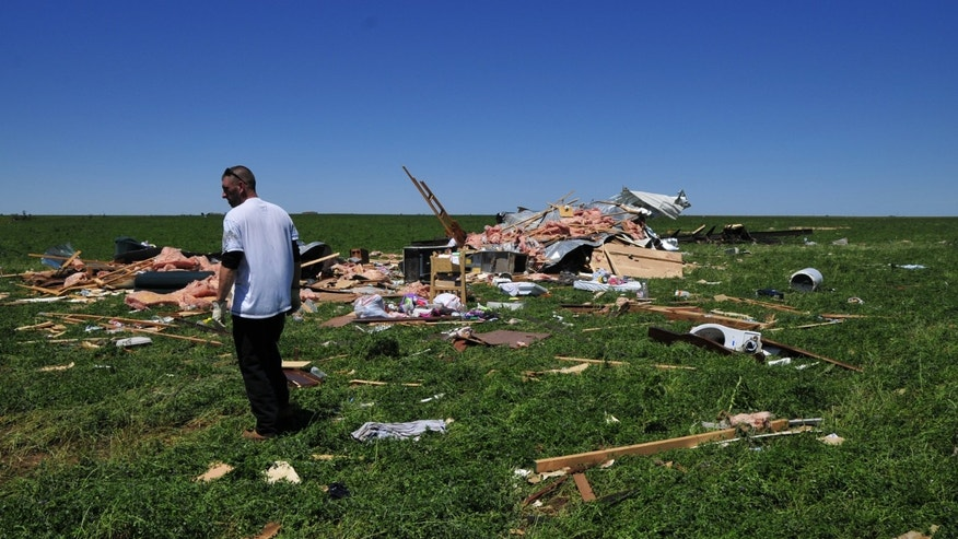 Joshua Lamb stands near what was once he and his family's home that was left in ruins by a tornado, Saturday June 1, 2013 in El Reno Okla. (AP Photo/Nick Oxford)