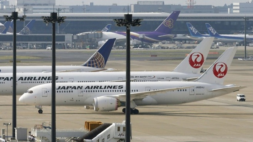 In this April 26, 2013 file photo, a Japan Airlines Boeing 787 plane, foreground, sits on a tarmac with others at Haneda Airport in Tokyo. A sensor problem was found Sunday, June 2, 2013 in one of the exchanged batteries for a JAL Boeing 787 jet due to bound for Beijing from Haneda but did not pose a safety risk, a Japanese broadcaster reported.