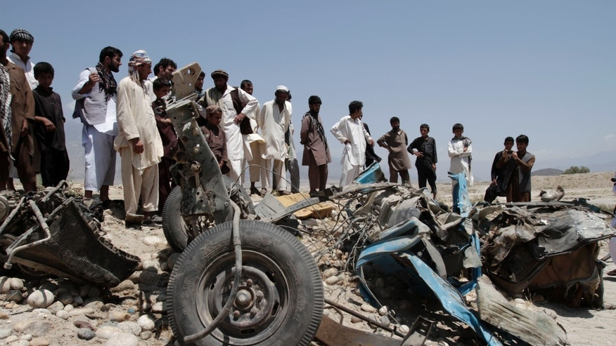 June 03, 2013. - Afghans look at a destroyed vehicle after it was hit by a road side bomb in the Alingar district of Laghman province, east of Kabul, Afghanistan.
