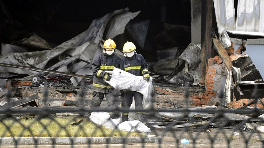 June 3, 2013 - Firefighters prepare bags that appear to contain the remains of victims from a poultry processing plant that was engulfed by a fire in northeast China's Jilin province.