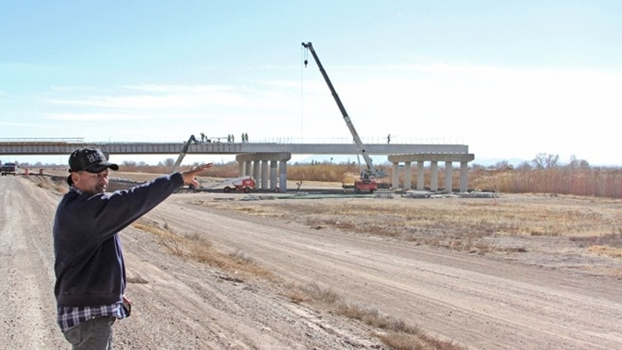 Jesse Grado, superintendent of a bridge construction site, points at corn fields across the Rio Grande at the at the Tornillo-Guadalupe border bridge construction in Tornillo, Texas, Friday, Jan. 18, 2013. The bi-national project is nearly finished in the U.S. side, while work has not started on the Mexican side of the river. (AP Photo/Juan Carlos Llorca)