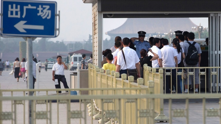 "June 3, 2013 - A Chinese policeman reacts as visitors to Tianamen Square wait for security screening near a sign which reads ""Exit Square"" on the eve of the 24th anniversary of the bloody military crackdown on protesters in Beijing."