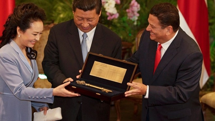 "China's President Xi Jinping, center, and his wife Peng Liyuan hold the ""Key to the City"" given to them by San Jose Mayor Johnny Araya in San Jose, Costa Rica, Monday, June 3, 2013. After Costa Rica, Xi has planned stops in Mexico and the United States. Trinidad, a leading supplier of natural gas, was his first stop of a four-country trip in the region. (AP Photo/Arnulfo Franco)"