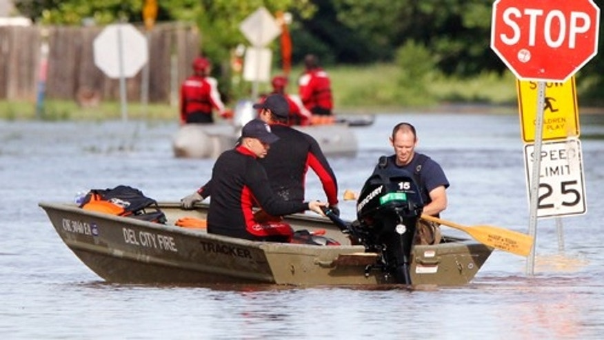 Crews use boats to rescue residents from a flooded mobile home park in Midwest City, Okla, Saturday, June 1, 2013, after up to eight inches of rain fell during the previous 24 hours.