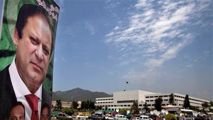 June 5, 2013: A banner with the portrait of Pakistan's upcoming Prime Minister Nawaz Sharif, is displayed near the National Assembly building, background, in Islamabad, Pakistan.
