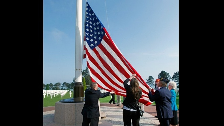 June 6, 2013: Members of the American Legion raise the U.S. flag at the Colleville American military cemetery, in Colleville sur Mer, western France on the day of the commemoration of the 69th anniversary of the D-Day.