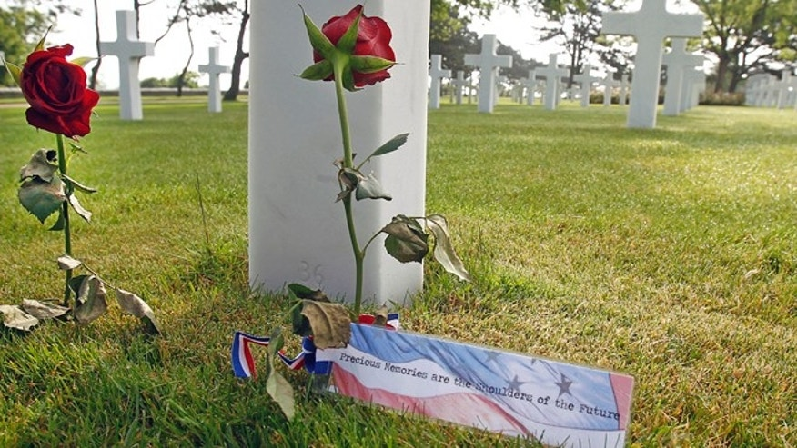 June 6, 2013: Roses are laid on one of the 9,387 graves at the Colleville American military cemetery, in Colleville sur Mer, western France, Thursday on the day of the commemoration of the 69th anniversary of the D-Day.