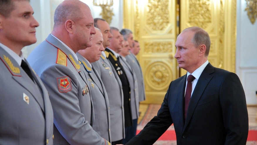 Russian President Vladimir Putin, right, shakes hands at the presentation ceremony of the top military brass in the Kremlin in Moscow, Friday, June 7, 2013. (AP Photo/RIA-Novosti, Alexei Nikolsky, Presidential Press Service)