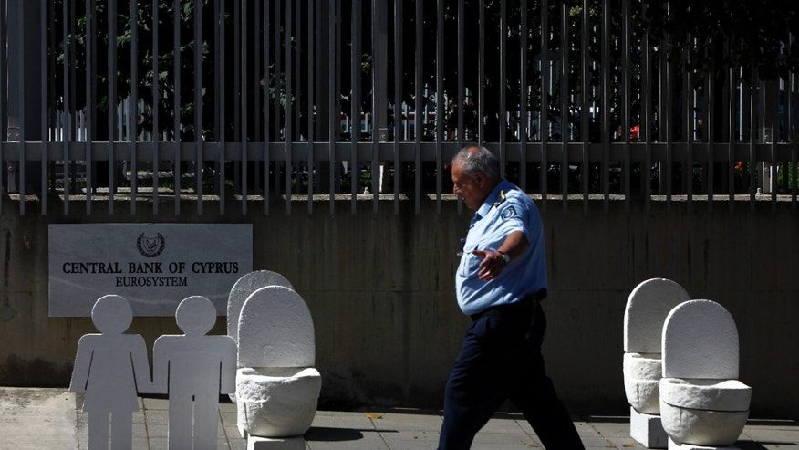 June 10, 2013 - A police officer reacts as he walks past the white-gray plaster and perlite creations that look like toilets outside of the gate of Cyprus central bank building in Nicosia, Cyprus.