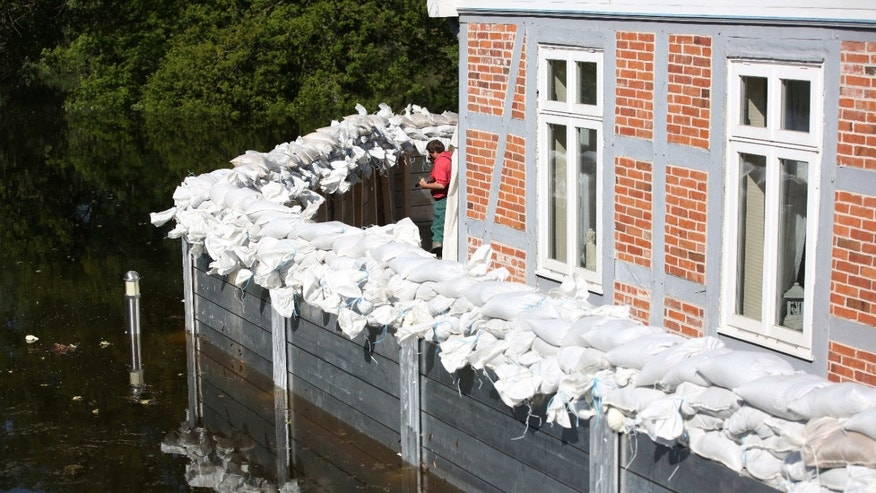 June 10, 2013 - A helper controls a wall erected to protect a restaurant from Elbe floodwater in Lauenburg, northern Germany.