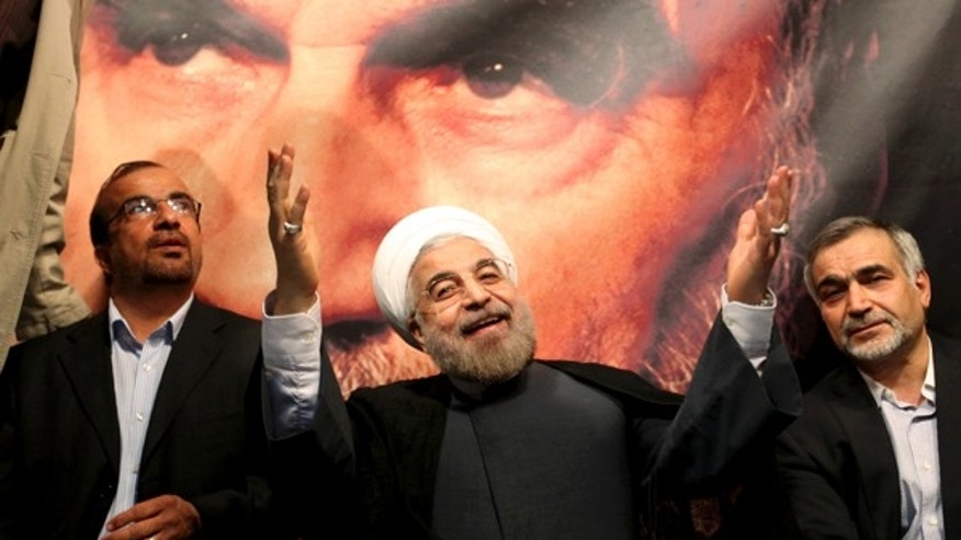 June 1, 2013: This photo shows, in front of a portrait of the late Iranian revolutionary founder Ayatollah Khomeini, presidential candidate Hasan Rowhani, a former top nuclear negotiator, center, gestures to his supporters at a rally in Tehran, Iran. Iranian pro-reform candidate, Mohammad Reza Aref, pulled out of this week's presidential election to give support to a centrist whose campaign has gained momentum in recent days. The decision by Aref is seen as a major boost for Hasan Rowhani, who now faces off against five conservative candidates Friday.