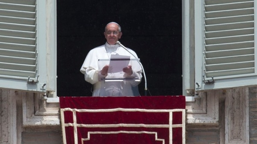 June 9, 2013: Pope Francis reads a message during the Angelus noon prayer he celebrated from the window of his studio overlooking St. Peter's square at the Vatican