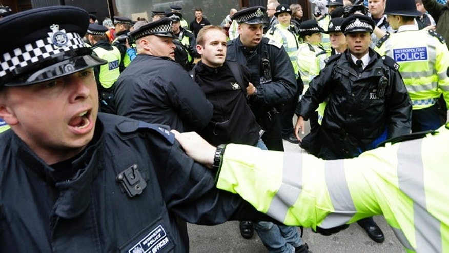 June 11, 2013: A demonstrator is take to a police vehicle after he was detained during a protest in London.The protestors were demonstrating against the upcoming G8 summit in Northern Ireland on June 17 and 18.
