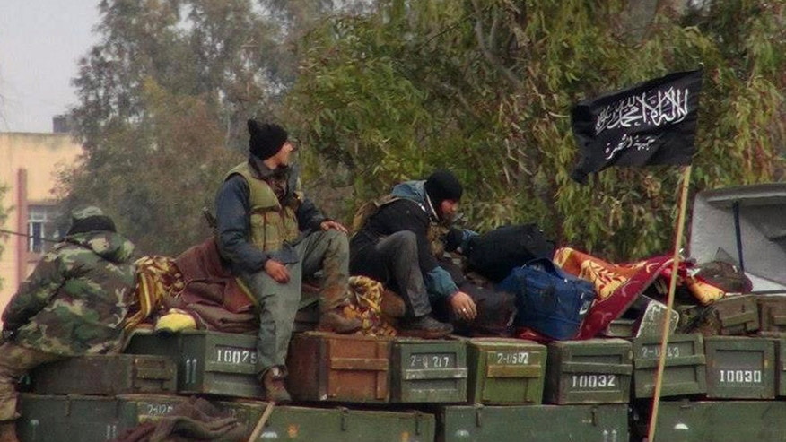 Rebels from Al-Qaeda affiliated Jabhat al Nusra, as they sit on a truck full of ammunition, at Taftanaz air base,  that was captured by the rebels, in Idlib province, northern Syria. (AP Photo/Edlib News Network ENN, File)