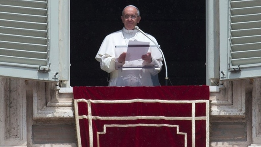June 9, 2013: Pope Francis reads a message during the Angelus noon prayer he celebrated from the window of his studio overlooking St. Peter's square at the Vatican.