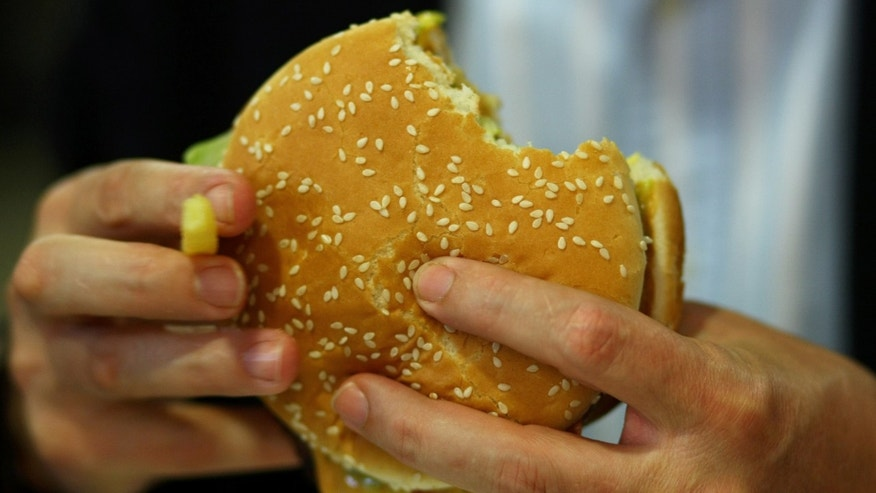 MUNICH, GERMANY - JUNE 15: A man eats a Whopper  during the opening of  the first European Whopper Bar on June 15, 2009 in Munich, Germany. Customers can choose from over 20 toppings  for their Whopper burgers.  (Photo by Miguel Villagran/Getty Images)
