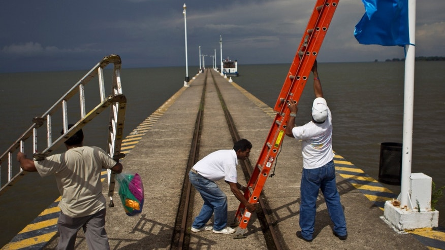 June 7, 2013 - Workers position a ladder to hang a banner on a wharf surrounded by Lake Nicaragua, in Granada, Nicaragua. A multi-billion dollar Chinese plan to plow a massive rival to the Panama Canal across the middle of Nicaragua was headed for approval by the leftist-controlled National Assembly.