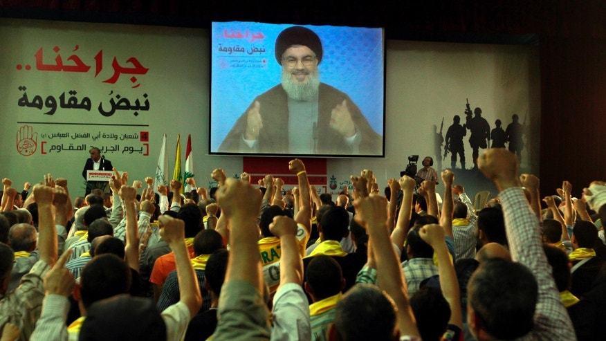 "June 14, 2013 - Hezbollah supporters raise their hands in salute as Hezbollah leader Sheik Hassan Nasrallah speaks on a screen via a video link from a secret place, during a rally to mark the ""wounded resistants day"" in the southern suburb of Beirut, Lebanon."