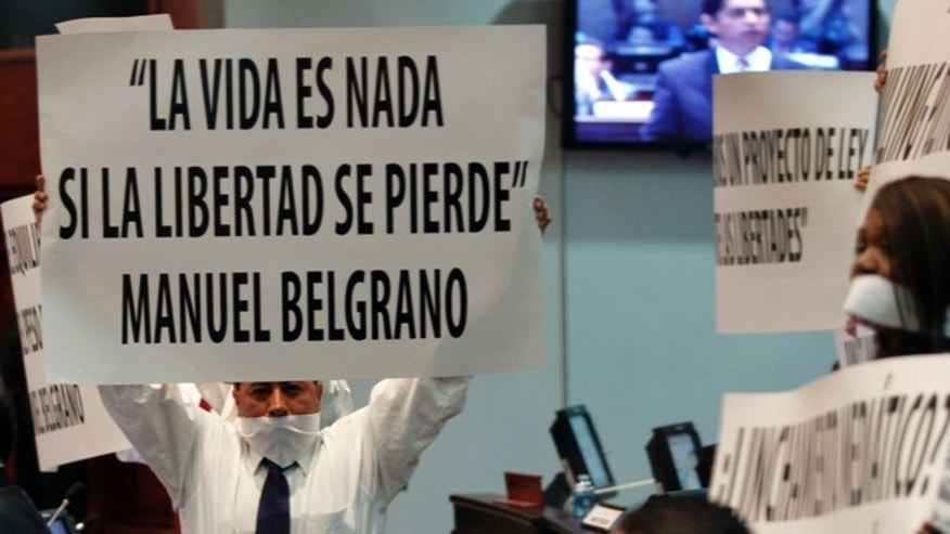 """Opposition lawmakers wearing gags hold up posters that read in Spanish """"Life is nothing if you loss freedom"""" Manuel Belgrano, as they protest a new Communications Act during the voting at Congress in Quito, Ecuador, Friday, June 14, 2013. Ecuador's congress on Friday passed a restrictive new media law championed by President Rafael Correa, creating official media overseers, imposing sanctions for smearing """"people's good name"""" and limiting private media to one third of radio and TV licenses. (AP Photo/Dolores Ochoa)"""