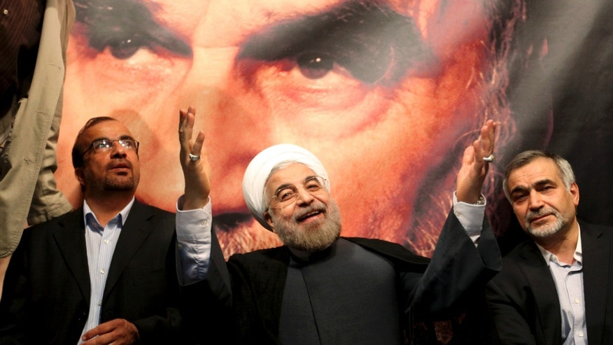The U.S. may be hoping Iran's new president-elect, Hasan Rowhani, shown here in front of a portrait of the late Iranian revolutionary founder Ayatollah Khomeini, will be amenable to talks. (AP)